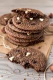 Schokoladenplätzchen mit Haselnüssen, weißer Schokolade und dunkler Schokolade auf Pergament, hölzerner Hintergrund, vertikal Lizenzfreie Stockfotos