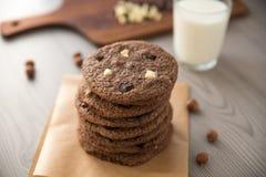 Schokoladenplätzchen mit Haselnüssen, weißer Schokolade und dunkler Schokolade auf Pergament und Glas Milch, hölzerner Hintergrun Stockfotografie