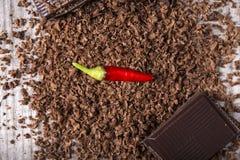 Schokoladenraspel mit rote Paprika-Pfeffer auf Holz Lizenzfreies Stockfoto