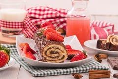 Schokoladenrolle mit Haselnüssen und Erdbeeren Lizenzfreies Stockfoto