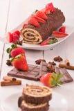 Schokoladenrolle mit Haselnüssen und Erdbeeren Stockbild