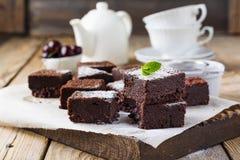 Schokoladenschokoladenkuchen mit Puderzucker und Kirschen auf einem dunklen hölzernen Hintergrund Stockfotografie