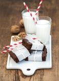 Schokoladenschokoladenkuchenscheiben eingewickelt in Papier- und in müdem mit Seil, Gläser Milch, Streifenstrohe, Walnüsse auf we Stockfotos