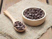 Schokoladensplitter im hölzernen Löffel und in der Schüssel Stockbild