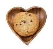 Schokoladensplitterplätzchen auf dem Herzen formte hölzerne Platte Stockfoto