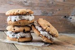 Schokoladensplitterplätzchen-Eiscremesandwiche gegen rustikales Holz stockbild