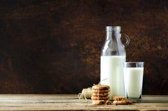 Schokoladensplitterplätzchen, -flasche und -glas Milch auf Holztisch, dunkler Hintergrund Sonniger Morgen, Kopienraum Stockfotos