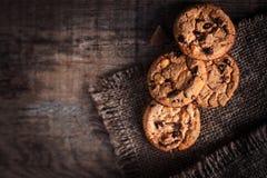 Schokoladensplitterplätzchen, frisch gebacken auf rustikalem Holztisch S Lizenzfreie Stockbilder