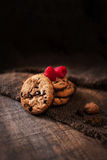 Schokoladensplitterplätzchen mit den Himbeeren Makro auf einem braunen backgr Lizenzfreies Stockfoto