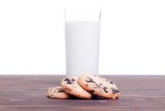 Schokoladensplitterplätzchen mit Milch auf der Seitenansicht des Brettes Stockfoto