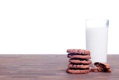 Schokoladensplitterplätzchen mit Milch auf der Seitenansicht des Brettes Stockfotografie