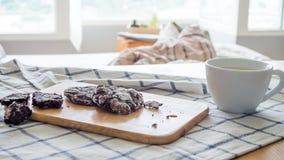 Schokoladensplitterplätzchen und eine Schale Milch Stockfoto