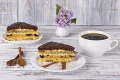Schokoladenstück des Kuchens vom Keksteig mit Mohn, Pflaume und Walnüsse und Tasse Kaffee Lizenzfreies Stockfoto
