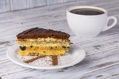 Schokoladenstück des Kuchens vom Keksteig mit Mohn, Pflaume und Walnüsse und Tasse Kaffee Stockfoto