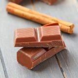 Schokoladenstücke mit Zimtstange auf hölzernem Hintergrund Stockfotografie