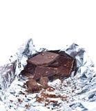Schokoladenstücke zerknittert in der Folie auf weißem Hintergrund stockbilder
