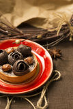 Schokoladentörtchen auf einer roten Platte mit Dekorationen Stockfotografie