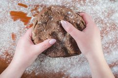 Schokoladenteig für Kuchen in den weiblichen Händen auf dem Hintergrund eines hölzernen Brettes, besprüht mit Weizenmehl lizenzfreies stockfoto