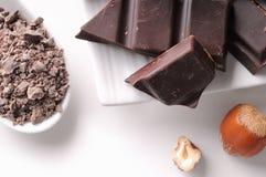 Schokoladenteile mit Haselnüssen auf einem Tellerabschluß oben Stockfotos