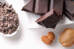 Schokoladenteile mit Mandeln auf einem Tellerabschluß oben Lizenzfreie Stockfotografie