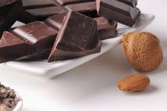 Schokoladenteile mit Mandeln auf einem Tellerabschluß oben Stockbild