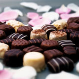 Schokoladentrüffeln und rosafarbene Blumenblätter Stockbilder