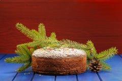 Schokoladenweihnachtsfruchtkuchen, Pelzbrunch und Kegel auf Blau und Lizenzfreie Stockfotos