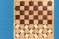 Schokoriegel braun und weiß auf einem Schachbrett Stockfotografie