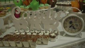 Schokoriegel Eine Tabelle mit süßen Süßigkeiten und Plätzchen in den grün-orange Tönen auf einem weißen Hintergrund stock video footage