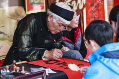 A scholar writes Chinese calligraphy characters at Temple of Literature. On Feb 12,2016.Calligraphy giving is a popular tradition during Tet holiday to royalty free stock photography