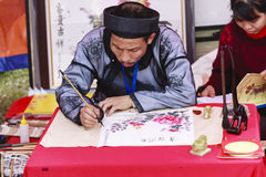 A scholar writes Chinese calligraphy characters at Temple of Literature. On Feb 12,2016.Calligraphy giving is a popular tradition during Tet holiday to royalty free stock photo