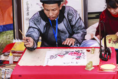 A scholar writes Chinese calligraphy characters at Temple of Literature. On Feb 12,2016.Calligraphy giving is a popular tradition during Tet holiday to stock image