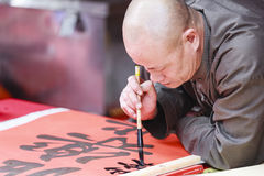 A scholar writes Chinese calligraphy characters at Temple of Literature. HANOI, VIETNAM - JAN, 26: A scholar writes Chinese calligraphy characters at Temple of royalty free stock image