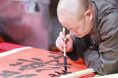A scholar writes Chinese calligraphy characters at Temple of Literature. HANOI, VIETNAM - JAN, 26: A scholar writes Chinese calligraphy characters at Temple of stock photos