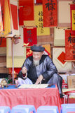 A scholar writes Chinese calligraphy characters at Temple of Literature. HANOI, VIETNAM - JAN, 26: A scholar writes Chinese calligraphy characters at Temple of royalty free stock photo