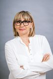 Scholarly attractive woman in glasses. Scholarly attractive middle-aged blond woman in glasses standing looking at the camera with folded arms against a grey Stock Photos