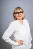 Scholarly attractive woman in glasses. Scholarly attractive middle-aged blond woman in glasses standing looking at the camera with folded arms against a grey Royalty Free Stock Images