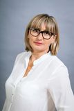 Scholarly attractive woman in glasses. Scholarly attractive middle-aged blond woman in glasses standing looking at the camera with folded arms against a grey Stock Image