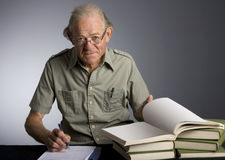 Scholarly Mature Man. Studio photo of scholarly mature caucasian male taking noted from textbooks Royalty Free Stock Photos