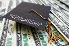 Scholarship cap on money stock image