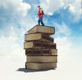 The concept of scholarship and opportunity. Kid standing on top of a stack of books.The concept of scholarship royalty free stock photo
