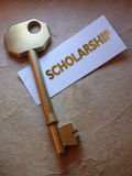 Scholarship concept. Scholarship label and golden key close up royalty free stock photo