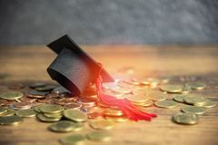 Scholarship for education concept graduation cap on money coin wooden table. Scholarship for education concept with graduation cap on money coin wooden table royalty free stock images