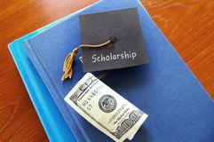 Scholarship graduate and books. Scholarship graduation cap with money on a pile of books Stock Images