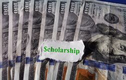 Scholarship hundreds. Torn paper with Scholarship text on hundred dollar bills Royalty Free Stock Photo