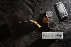 Scholarship money concept. Scholarship message with graduation cap and money royalty free stock image