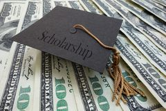Scholarship money. Mini graduation mortar board with Scholarship text, on money royalty free stock photography