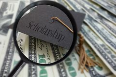 Scholarship money search. Magnified graduation mortar board with Scholarship text, on money Stock Images
