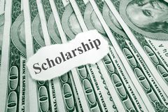 Scholarship money. Scholarship text on paper, over hundred dollar bills royalty free stock photo