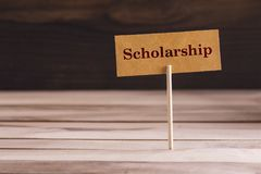 Scholarship word sign. Scholarship word in Standing small sign on wood royalty free stock image